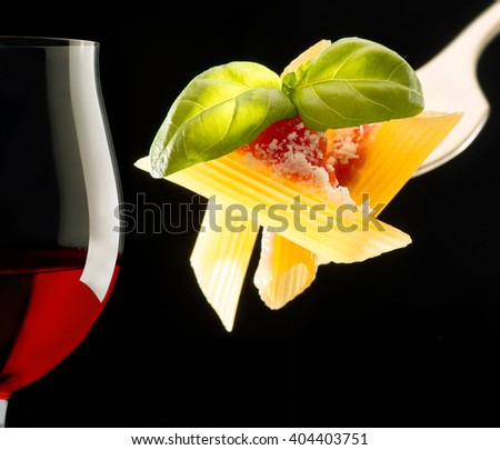 red wine glass and fork with macaroni on black background