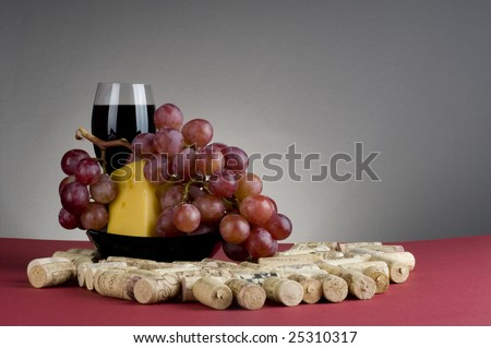 Red wine glass and grape with cheese on black plate next to  corks.