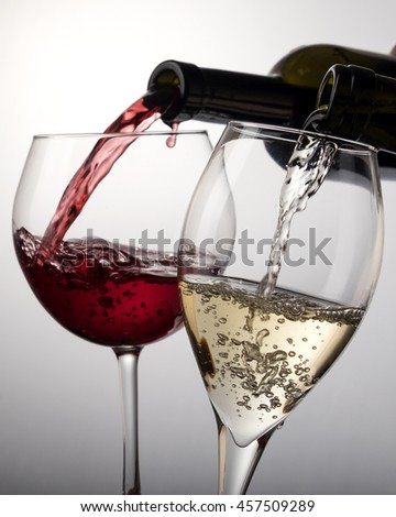 Red wine glass and white wine glass poured from bottles on white.
