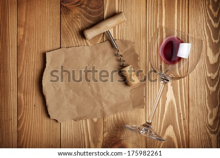Red wine glass, corkscrew and paper for your note on wooden table background - stock photo