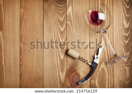 Red wine glass, corkscrew and wine cork on wooden table background with copy space - stock photo