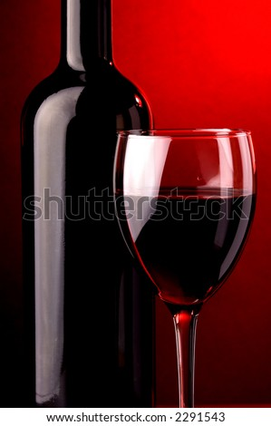 Red wine glass- detail and wine bottle detail. Low light and red background light.