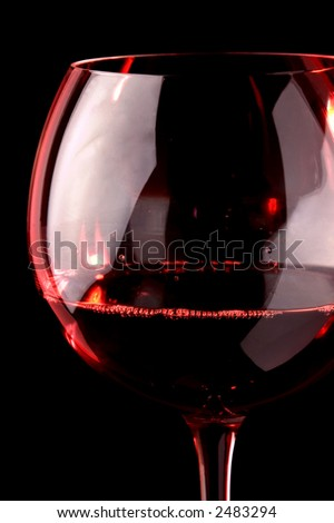 Red wine glass - detail. Black background , low red light on the wine glass.