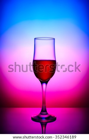 Red wine glass in blue magenta gradient background - stock photo