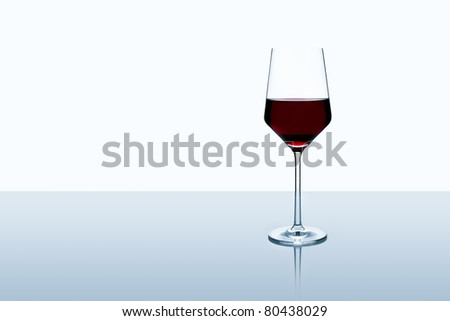 Red wine glass isolated on white background standing on a table - stock photo