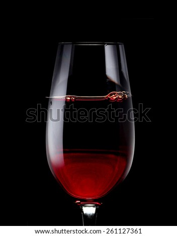 Red Wine Glass on Black Background with Bubbles - stock photo