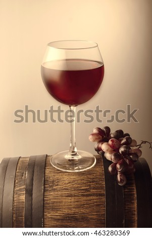 Red wine glass on old wooden barrel. Vintage style.