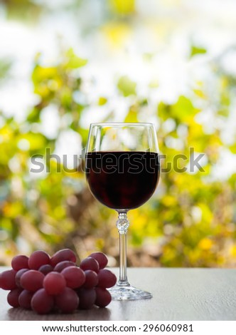 red wine glass on rustic wood surface with red grapes