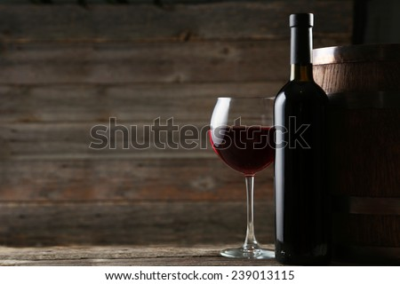 Red wine glass with bottle and barrel on grey wooden background - stock photo