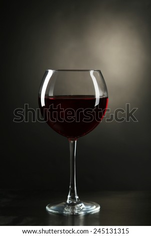 Red wine glass with bottle on black background - stock photo