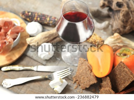 red wine glass with gourmet laid table in the background - stock photo