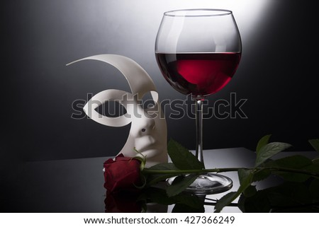 Red wine glass with red rose and mask - stock photo
