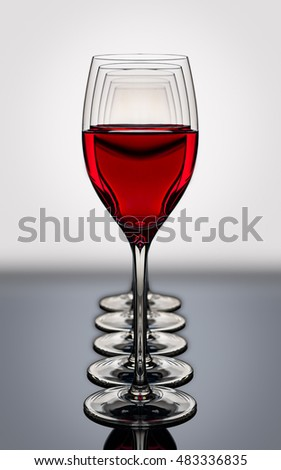 red wine glasses in a row backlighted on a reflective black board