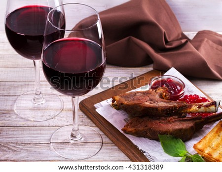 Red wine glasses. Rack of lamb with pomegranate sauce and greens