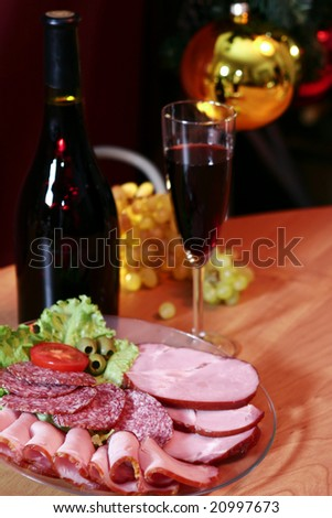 Red wine, grapes and meat on a New Year's background.