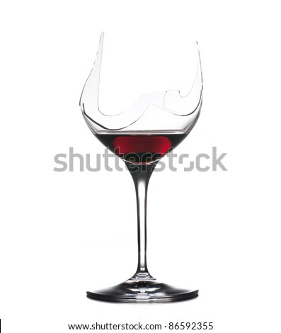 Red wine in a broken wine glass isolated against white - stock photo