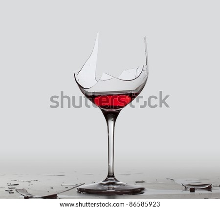 Red wine in a broken wine glass with a partial extraction path saved in the file - stock photo