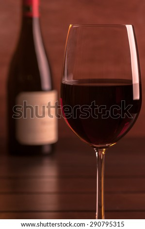 Red wine in a glass and wine bottle on a wooden table close up