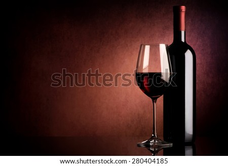 Red wine in bottle and wineglass on vinous background - stock photo