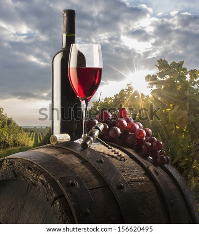 red wine in glass and bottle on old barrel - stock photo
