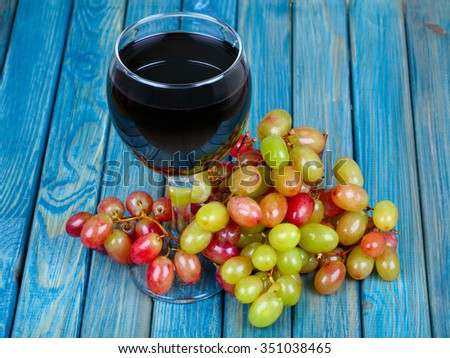 Red wine in glass and bunch of grapes on wooden table - stock photo