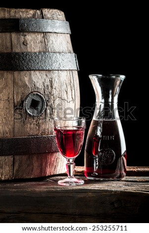 Red wine in glass and carafe in the old winery - stock photo
