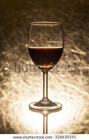 Red wine in glass on a gold background.
