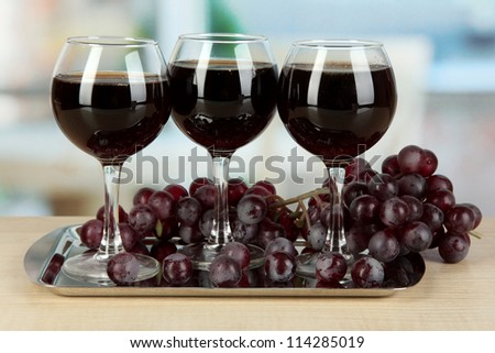 Red wine in glass on salver on room background - stock photo