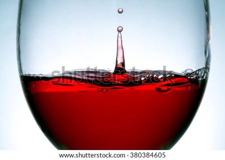 red wine in glass, splashing, splash, wave of red wine close up - stock photo