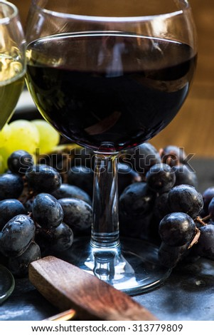 red wine in glass with fresh grapes and corkscrew - stock photo
