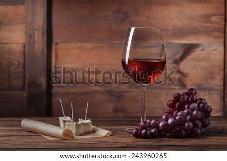 Red wine in glass with grape and cheese on wooden background - stock photo