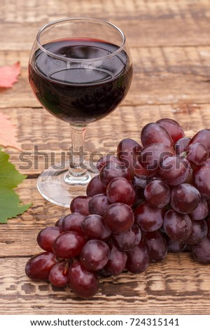 Red wine in glass with red grapes on wooden boards