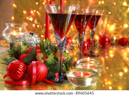 Red wine in glasses,baubles,candle lights,green twig and twinkle lights on golden background. - stock photo