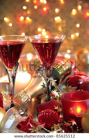 Red wine in glasses,bottle ,candle lights,baubles and twinkle lights on golden background. - stock photo