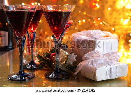 Red wine in glasses,gift boxes, green twig and baubles on gold background with twinkle lights. - stock photo
