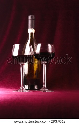 red wine in two glasses and bottle on a claret background