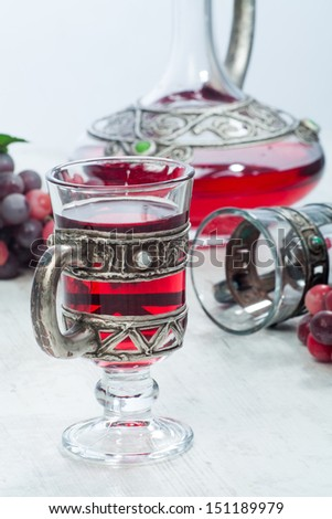 Red wine in vintage crystal and silver glassware, a crystal and silver decanter and red grapes besides. - stock photo
