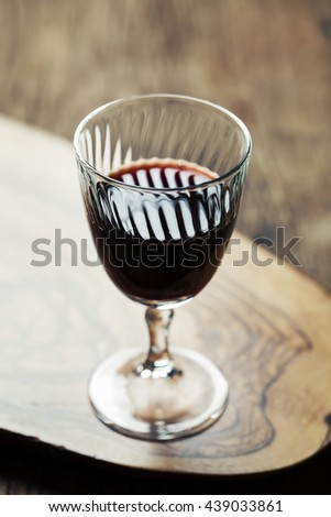 Red wine in vintage glass on olive wood background, toned