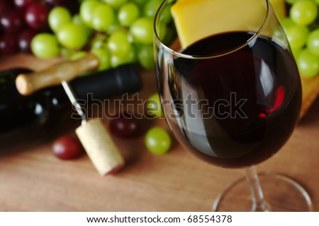 Red wine in wine glass with grapes, cheese a wine bottle and a corkscrew with cork in the background (Selective Focus, Focus on the front of the rim of the wine glass) - stock photo