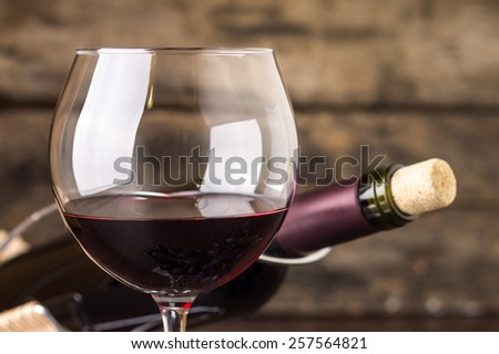 Red wine in wineglass against corked bottle on wood background - stock photo