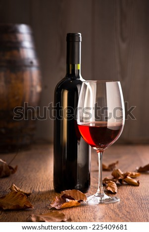 Red wine in wineglass and bottle with vintage barrel and fallen leaves. - stock photo