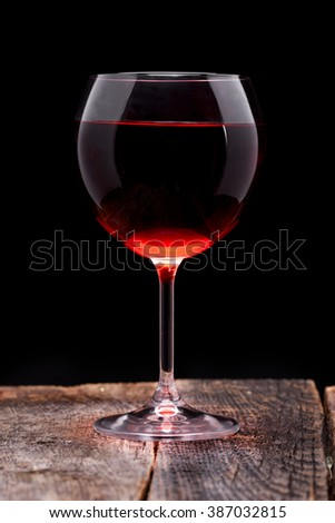 Red wine into the glass in wooden table - stock photo