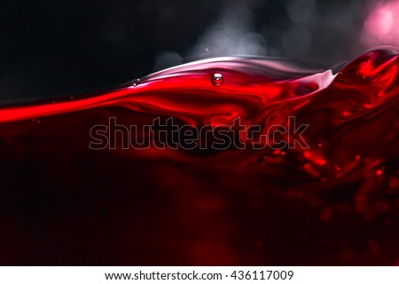 Red wine on black background, abstract splashing. - stock photo