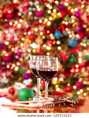 Red wine on Mahoney table with bright Christmas tree lights in background.  Vertical format layout.