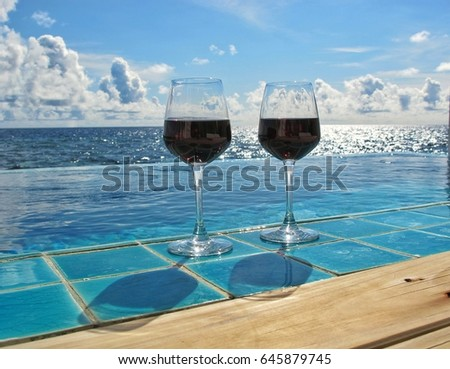 Red wine on sky and sea background.