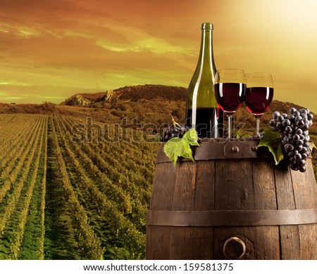 Red wine on wooden keg with vineyard on background - stock photo