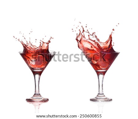 Red wine or alcohol cocktail splashing out of a glass, isolated on white. Make splash