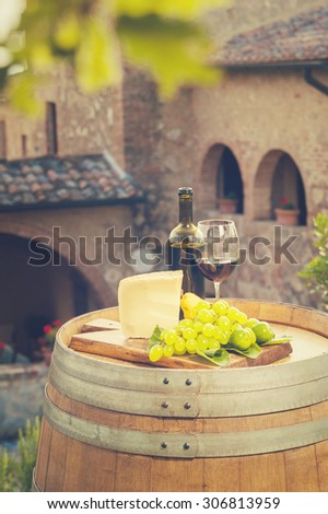 Red wine, pecorino cheese, grapes, bottle and glass on wooden barrel in the background of the Tuscan landscape, Italy - stock photo
