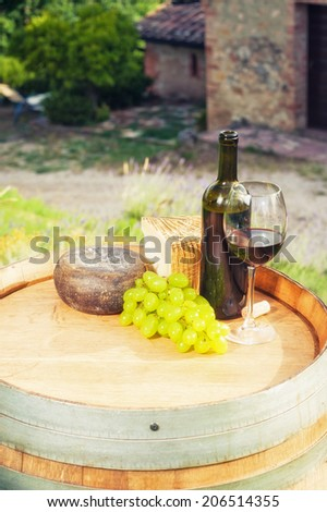 Red wine, pecorino cheese on a wooden barrel in the background of the Tuscan landscape, Italy