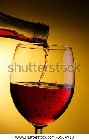 Red wine pour into glass close-up over yellow background